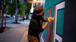 ezra dickinson painting a wall in seattle
